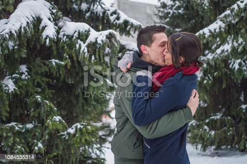 Young couple is in a winter forest while snow is falling.