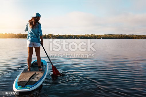 Shot of a young woman paddle boarding on a lake
