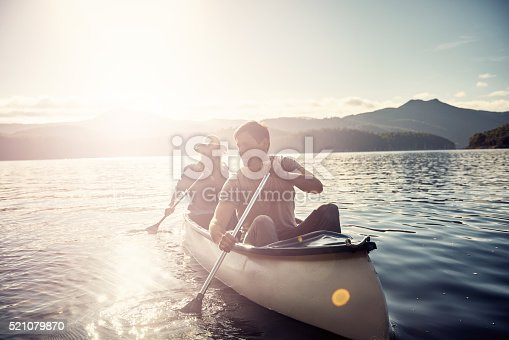 Shot of a young couple rowing a boat out on the lake