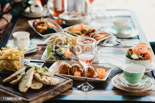 A table filled with delicious looking food served in different sized dishes alongside quirky teacups and glasses of wine.
