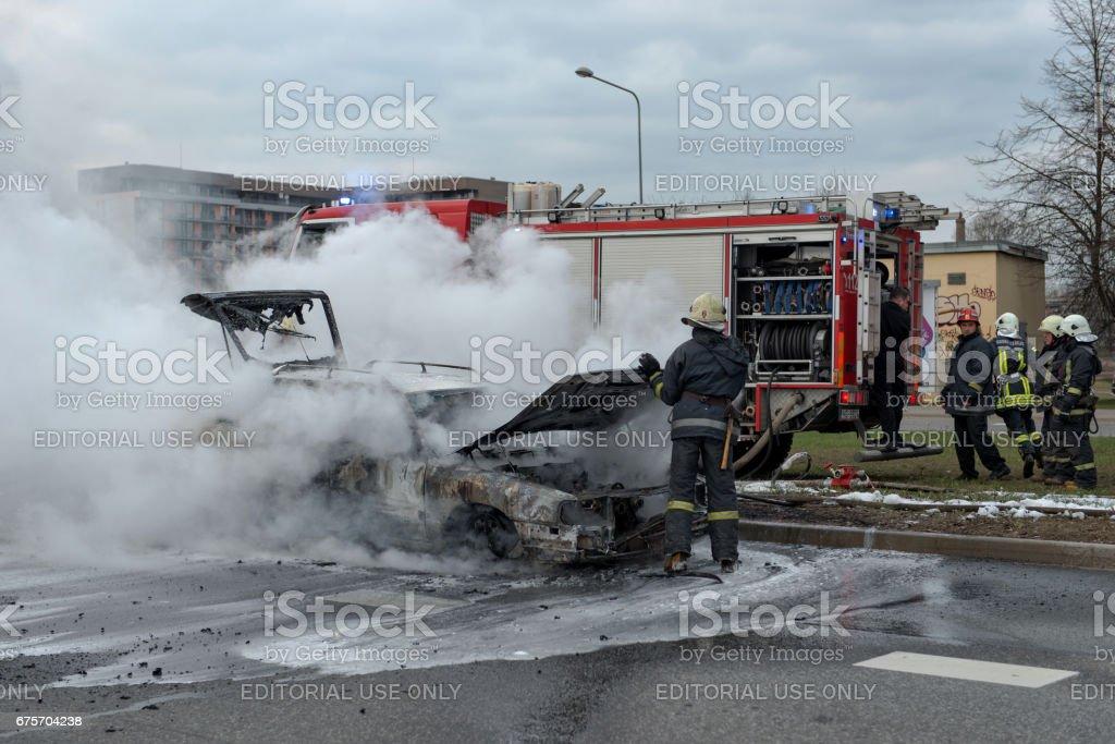 出到燒車的道路。消防人員已經趕到了。要去滅火工程。交通是停止了。 免版稅 stock photo