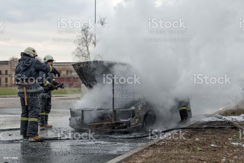 出來到馬路站只是浸的車。消防員視察損失。 免版稅 stock photo