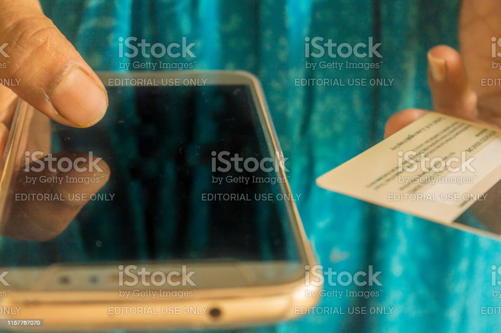 Out Of Focus Asian And Indian Woman Paying Bill At Home With