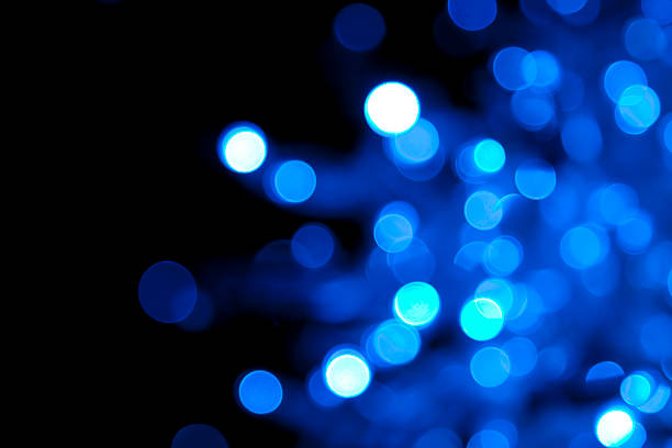 out of focus illuminated blue dots on black background - disco lights stock photos and pictures