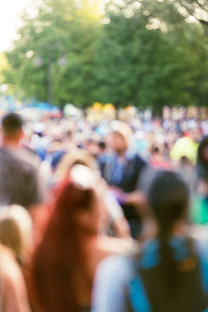 out of focus large crowd at outdoor event stock photo