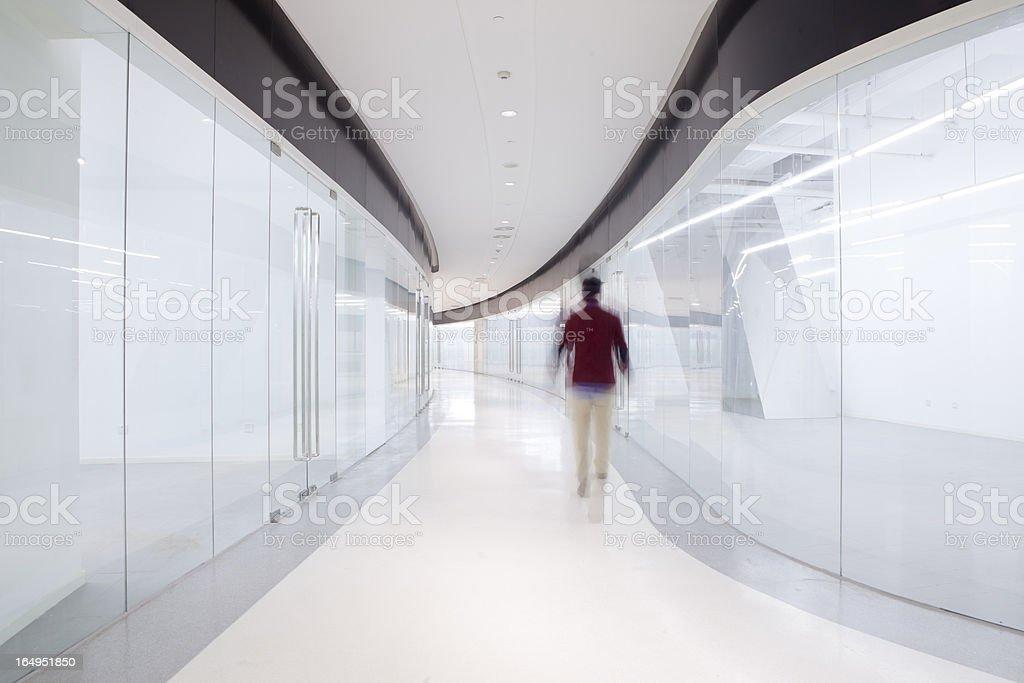 Out of focus man walking down modern corridor royalty-free stock photo
