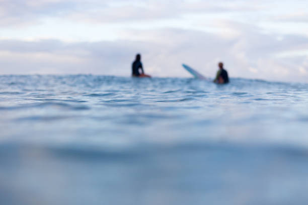 Out of focus surfers on the horizon stock photo