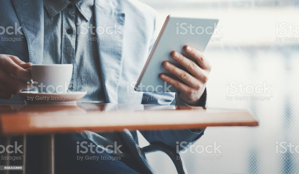 Closeup front view of unrecognizable businessman having coffee at...