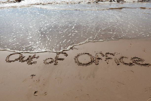 out of office written in the sand on a beach. - after work stock photos and pictures