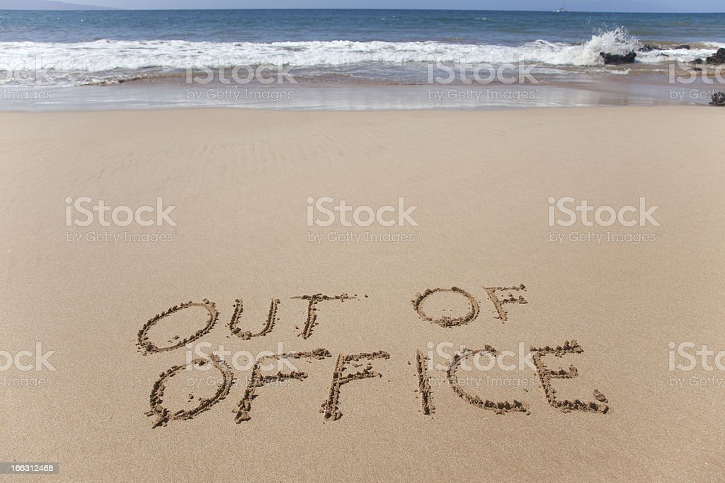 Out of office written in the sand on a beach stock photo