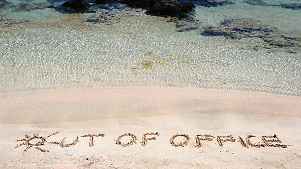 out of office written on sand on clear beach - after work stock photos and pictures