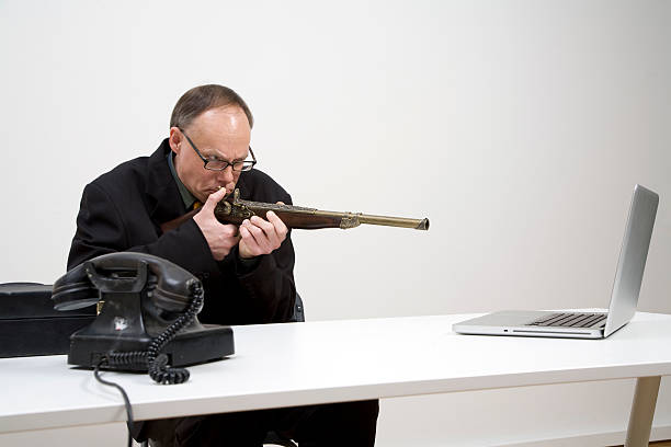 Out of touch and angry Businessman wants to shoot a modern laptop with an ancient gun.  Note the ancient phone.  Berlin Uberlypse 2009 anachronistic stock pictures, royalty-free photos & images