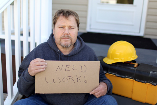 Construction worker by trade holding sign that he needs work.