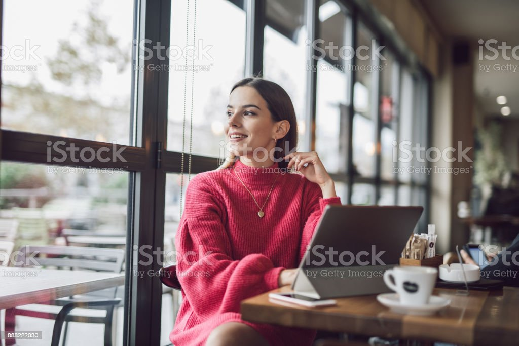 Young and beautiful businesswoman sitting in the cafe,drinking coffee...