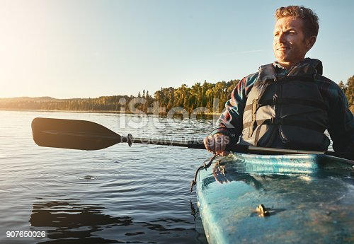 Shot of a young man kayaking on a lake outdoors