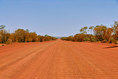 A long straight but rough red dirt road in the outback of the Northern Territory of Australia