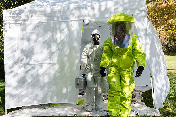 Outbreak Two healthcare workers depart to the scene dressed in their hazmat gear. decontamination stock pictures, royalty-free photos & images