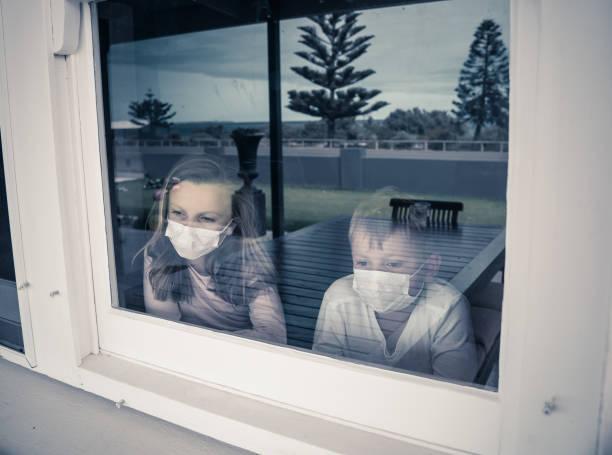 COVID-19 Ausbruch. Traurige kranke Kinder mit Gesichtsmaske, die während der Quarantäne zu Hause durch das Fenster schauen. Coronavirus Isolation und psychische Gesundheit der Kinder. – Foto
