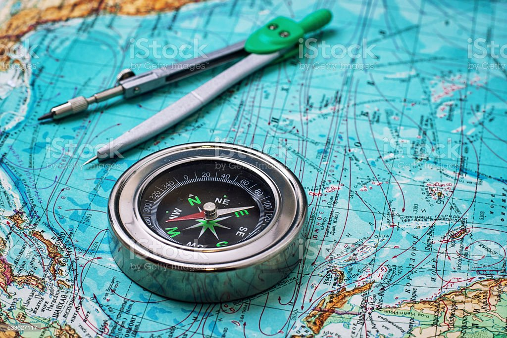 outdated compass sailor on topographic map stock photo