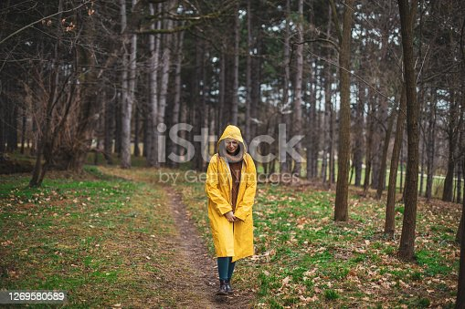 A woman is enjoying a rainy day in nature. She is walking with her arms crossed in a yellow raincoat in the woods and looking down at the road.