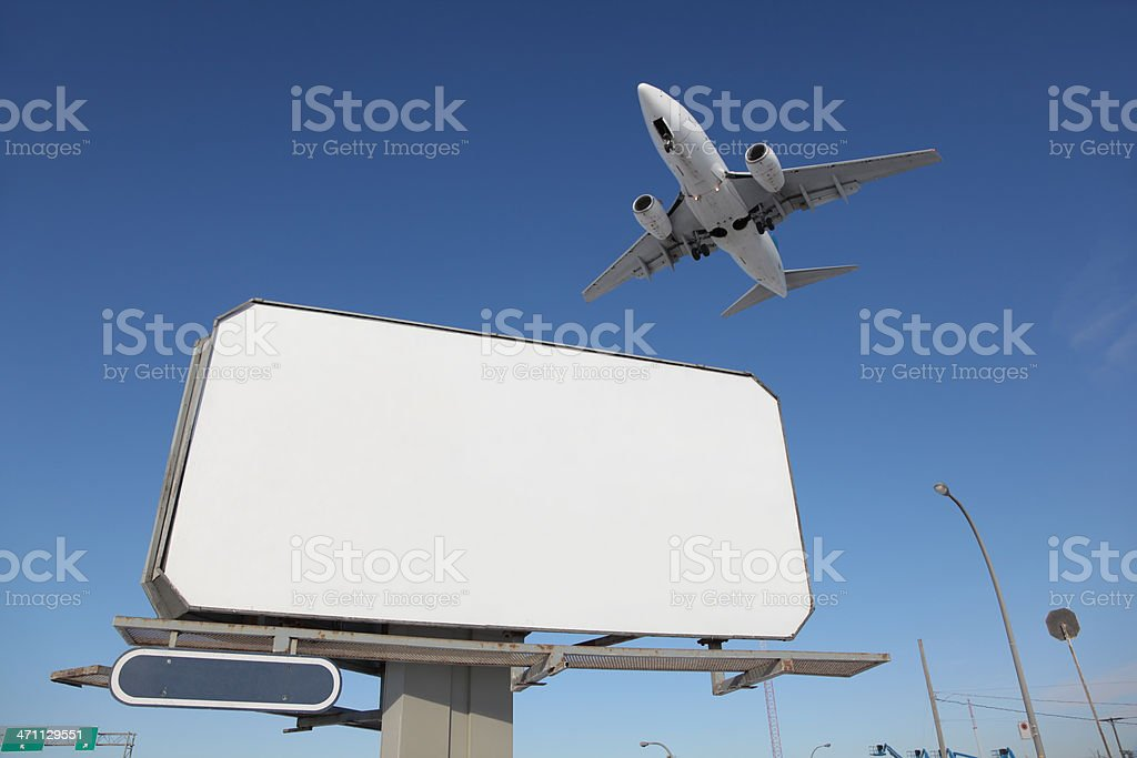 Outdoor Advertising Sign with Airplane passing above royalty-free stock photo