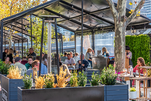 Melbourne, Victoria, Australia, April 17th, 2021: Diners are enjoying the outdoor al fresco dining restaurants that utilise the promenade space along the Yarra river in Southbank Melbourne.