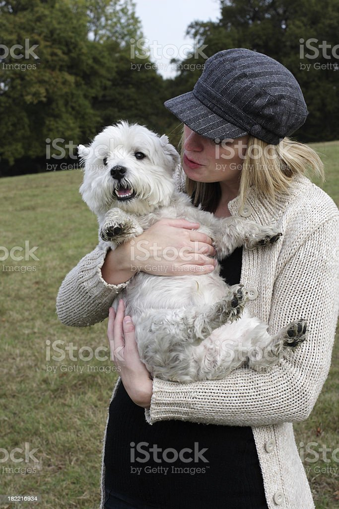 Fair haired Surrey girl kissing Beno her Westie royalty-free stock photo