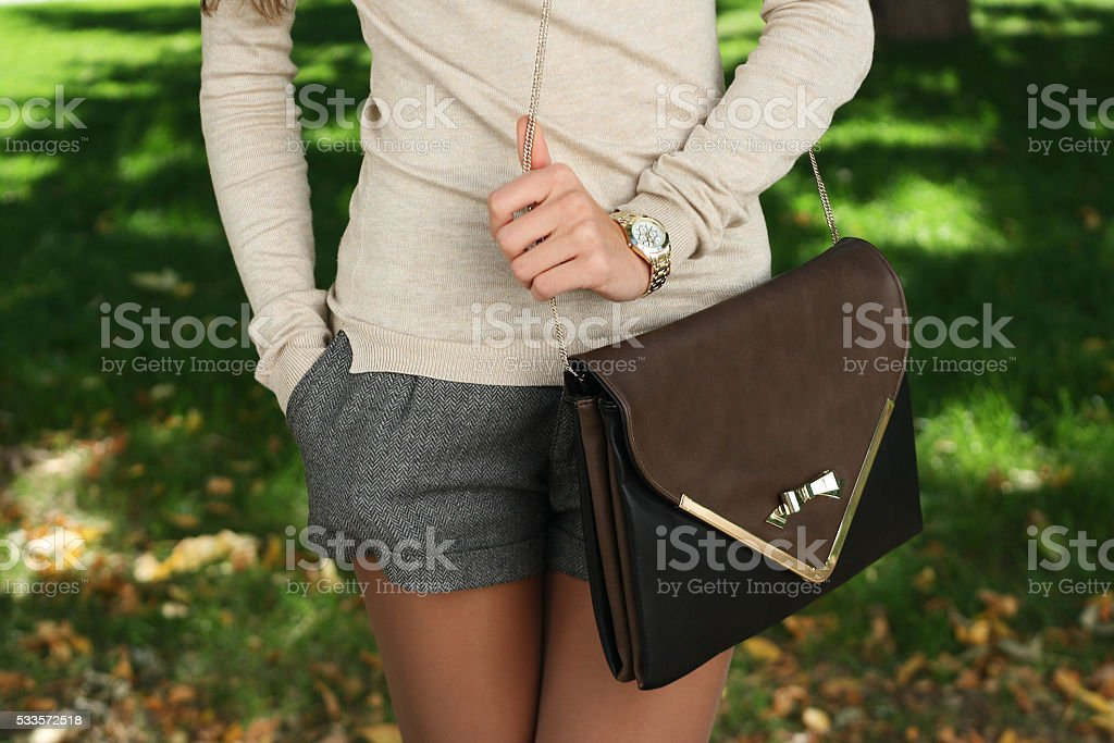outdoor autumn young trendy girl  with handbag clutch walking stock photo