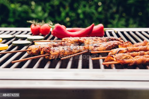 Barbecue grill outdoors in a back yard with greenery, with chicken and jalapenos grilling
