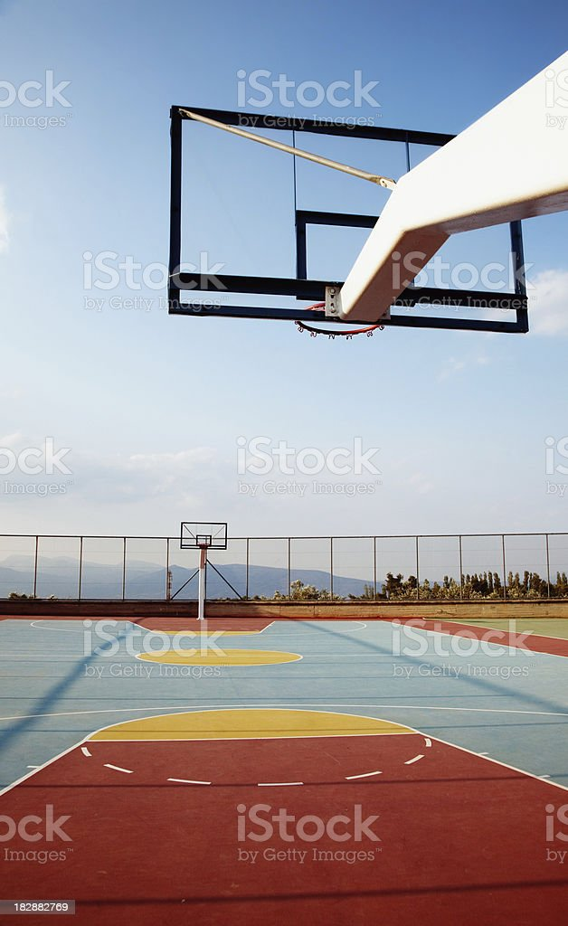 Outdoor basketball court. Evening light.