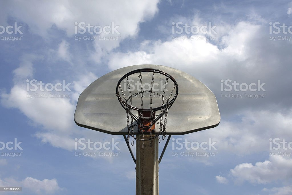 Outdoor Basketball Hoop against a Cloudy Sky stock photo