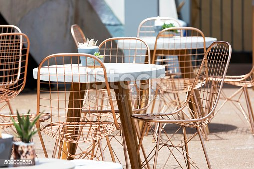 Outdoor cafe with round tables and aluminium modern chairs, full frame horizontal composition
