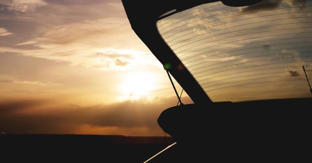 outdoor-autostamm bei sonnenuntergang, foto gegen die sonne - hecktürmodell stock-fotos und bilder