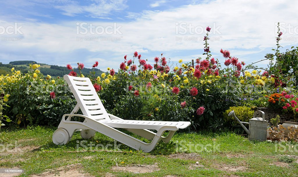 white outdoor chair in garden at a background of red and yellow...