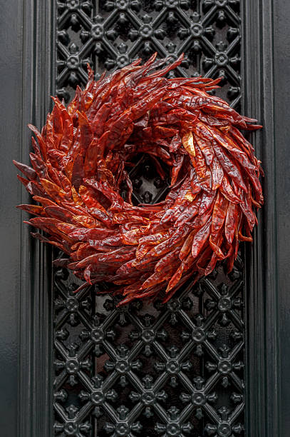 outdoor christmas wreath made of dried red hot chili peppers - ferien tür kränze stock-fotos und bilder