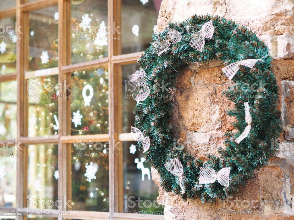 outdoor christmas wreath with bow ribbon hang on the concrete wall for window shop decoration