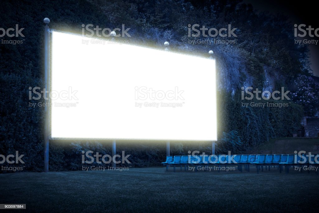 Outdoor cinema with chairs and white projection screen in nature - image with copy space'n stock photo