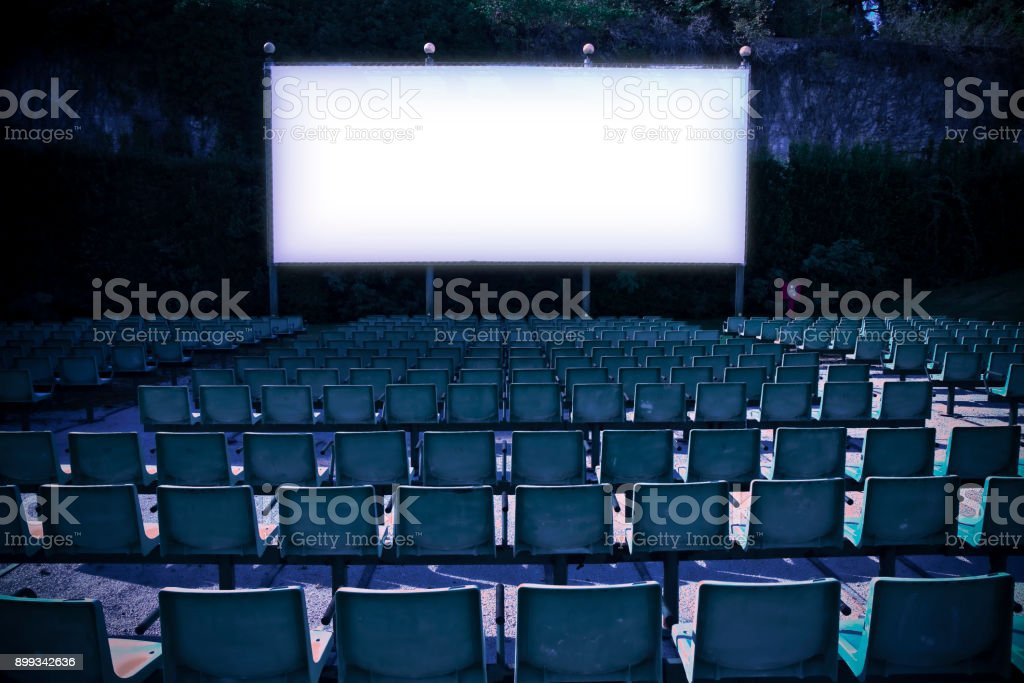 Outdoor cinema with white projection screen - toned image stock photo