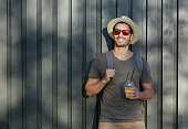 Outdoor closeup of young trendy European man standing alone with grey wooden fence behind, looking around with fresh drink in hand, having backpack on, feeling relaxed and eager to continue journey