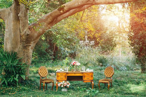 Outdoor composition consisting of two antique chairs and table set for two people and decorated with bouquets of flowers