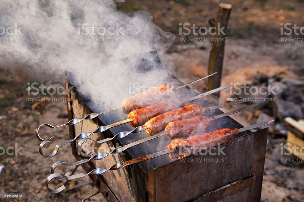 Outdoor cooking. Tasty sausages grilled on a brazier stock photo