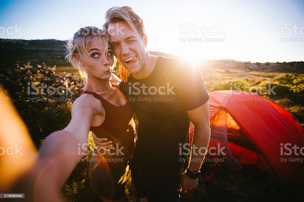 Outdoor couple taking sunset selfie while camping on hiking vaca stock photo