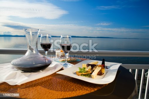 Inviting cheese and wine for two, overlooking the river at sunset.