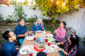 Diverse group of friends having dinner outdoors at a backyard bbq