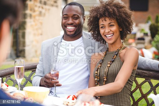 Young couple sitting around a table at a dinner party, enjoying scones and champagne.