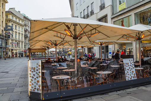 Vienna, Austria - October 2019: Outdoor electric heating infrared lamps under umbrella in street cafe in cold autumn season