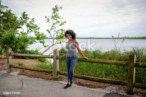 Beautiful African American woman with big natural hair, takes a break from a workout   and leans against a fence, she is in exercise gear and sneakers along a scenic pedestrian path