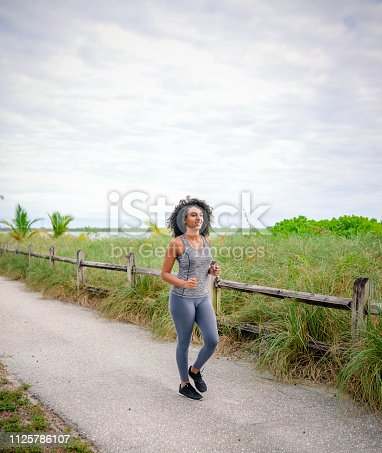 Beautiful African American woman with big natural hair, power walks in workout gear and sneakers along a scenic pedestrian path