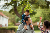 A family of three are on a walk outdoors whilst the father is giving his mixed-race son a piggyback