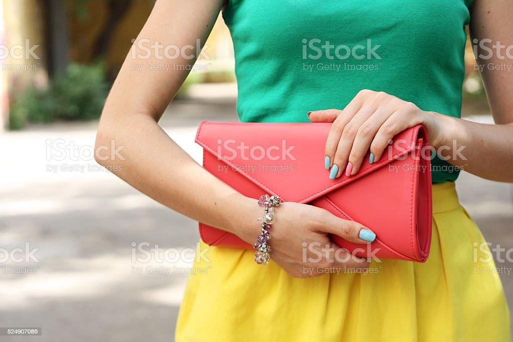 Outdoor fashion girl with coral orange handbag clutch stock photo